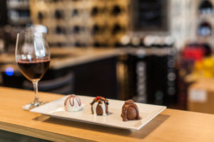 glass of wine and plate of chocolate truffles