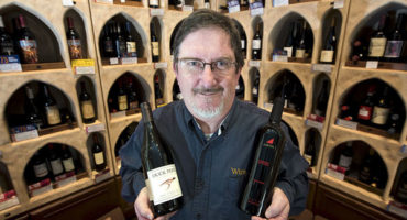 Jerry Janssen holding two bottles of wine