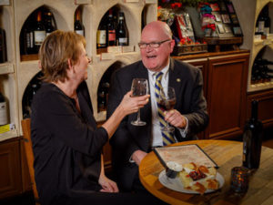 couple toasting wine and eating at table